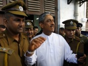 Jailed former army Chief Sarath Fonseka arrives with prison officers at the high court in Colombo