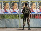 A soldier looks at campaign posters of Sri Lankan President Mahinda Rajapakse, in Colombo