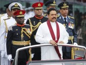 Sri Lanka's President Mahinda Rajapaksa inspects troops from an army vehicle during a war victory ceremony in Colombo