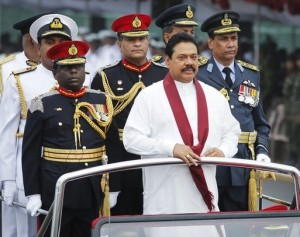 Sri Lanka's President Mahinda Rajapaksa (front, in white) inspects troops from an army vehicle in a parade during a war victory ceremony in Colombo May 27, 2011. Sri Lanka holds a military parade and memorial for fallen soldiers on Friday to mark the second anniversary of the defeat of the Tamil Tigers, which ended a quarter-century civil war in the Indian Ocean nation. Pictured with Rajapaksa are Navy Chief Somathilake Dissanayake (L, obscured), Army Chief Lieutenant General Jagath Jayasuriya (4th L, in dark uniform with red cap) and Defence Staff Air Marshal Roshan Gunetileke (R). REUTERS/Dinuka Liyanawatte (SRI LANKA - Tags: POLITICS MILITARY ANNIVERSARY CIVIL UNREST)