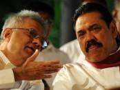 Sri Lankan President Mahinda Rajapakse (R) listens to Sri Lankan leader of the main opposition United National Party (UNP) Ranil Wickremesinghe during a Buddhist ceremony in Gangarama Temple in Colombo on February 6, 2012. Some 50 elephants, mostly from the central part of the island, together with thousands of traditional drummers, dancers, and monks gathered in the Sri Lankan capital to participate in the city's biggest two-day annual Buddhist procession starting February 6 to 7. The procession was first held in 1979. AFP PHOTO/Ishara S.KODIKARA (Photo credit should read Ishara S.KODIKARA/AFP/Getty Images)