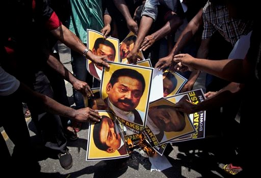 Supporters of Marumalarchi Dravida Munnetra Kazhagam (MDMK) burn portraits of Sri Lankan President Mahinda Rajapaksa during a protest in New Delhi, India, Monday, May 26, 2014. The protest was against Rajapaksa's visit, holding him responsible for the killing of innocent Tamils during the civil war in Sri Lanka. Rajapaksa along with other heads of state from across South Asia will be attending the swearing in ceremony of India's prime minister elect Narendra Modi, Monday. (AP Photo/Tsering Topgyal)