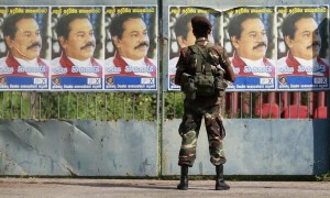 A soldier looks at campaign posters of Sri Lankan President Mahinda Rajapakse, in Colombo December 17, 2009. Rajapakse today submitted his applications for the January 26, 2010 presidential elections, with his main contender being Sri Lanka's retired general Sarath Fonseka. Sri Lanka's election commissioner on Thursday accepted a record 22 nominations for the January presidential poll, in which economic policies, and not war strategy, are expected to dominate the campaign.    REUTERS/Stringer  (SRI LANKA - Tags: POLITICS ELECTIONS)